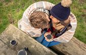 image of hot couple  - View from above of young couple under striped blanket and with hot beverage kissing outdoors in a cold day