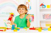 stock photo of kindergarten  - Cute little boy wearing glasses holding plastic hammer wrench and screwdriver - JPG
