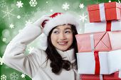pic of scratching head  - Portrait of happy girl scratching her head while holding christmas gifts with winter background - JPG