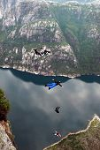 stock photo of parachute  - Man jumping off a cliff with a parachute - JPG