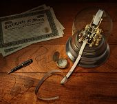 stock photo of stock market data  - Vintage stock brokerage desk with ticker tape machine simulated shares of stock candlestick telephone fountain pen pocket watch and library desk lamp - JPG