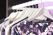 foto of boutique  - Female clothes collection on hangers in fashion boutique store - JPG