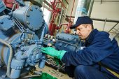 pic of plumber  - service engineer worker at industrial compressor refrigeration station repairing and adjusting equipment at manufacturing factory - JPG