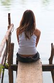 stock photo of dock  - Sad lonely teenage girl sitting on the small wooden dock on the river - JPG
