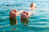 stock photo of splayed  - feet with splayed fingers lying on the water man - JPG