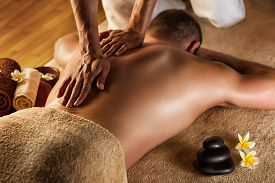 stock photo of deep  - Man has deep tissue massage on the back. Spa stones and frangipani flowers. ** Note: Shallow depth of field - JPG