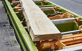 stock photo of sawing  - Sawing boards from logs with modern sawmill - JPG