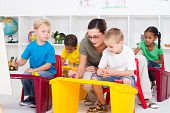stock photo of kindergarten  - kindergarten teacher helping young students with paintings in classroom - JPG