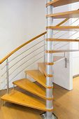 image of bannister  - morden spiral stairs with wooden steps inside a house - JPG