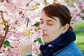 picture of hay fever  - woman smelling at almond tree - JPG