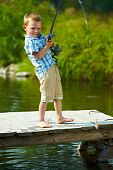 stock photo of spinner  - Photo of little kid pulling rod while fishing on weekend - JPG