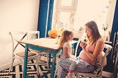 foto of baby bump  - happy pregnant mother playing with her baby daughter at home in kitchen - JPG