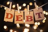 stock photo of lien  - The word DEBT printed on clothespin clipped cards in front of defocused glowing lights - JPG