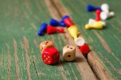 picture of figurines  - Horizontal photo of Few dices and color figurines for ludo placed on old wooden board with worn green color