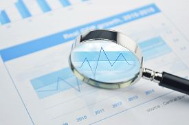 foto of analysis  - Magnifying glass over financial chart and graph business analysis concept - JPG