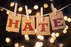 picture of hate  - The word HATE printed on clothespin clipped cards in front of defocused glowing lights - JPG