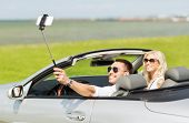 Постер, плакат: road trip leisure couple technology and people concept happy man and woman driving in cabriolet