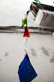 stock photo of yesteryear  - Different coloured flags hang from a balcony in Ibiza - JPG