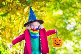 foto of halloween  - Little girl in witch costume playing in autumn park - JPG
