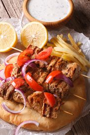 stock photo of souvlaki  - Greek souvlaki kebab with tomatoes and onions close - JPG