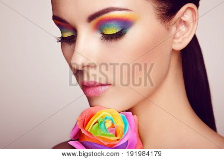 poster of Portrait of beautiful young woman with rainbow rose. Bright colors. Long eyelashes vivid colorful eyeshadows. Rainbow make up. Multicolored flowers