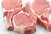stock photo of pork chop  - three plump center cut pork chops on white - JPG