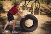 Determined girl exercising with huge tyre during obstacle course in boot campboot, camp, boot camp,  poster