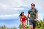 Hiking people hikers couple on nature trek walking on summer hike in mountains. Man trekking with wo poster