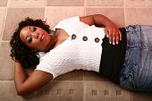stock photo of woman glamorous  - african american girl laying down on carpet and relaxing with one of her hand on back of her head showing blank expression - JPG