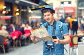Traveler With Trendy Look Using Map On Street Full Of Restaurants And Shops Of European City - Young poster