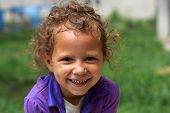 stock photo of gypsy  - poor and dirty but still happy and smiling cute little gypsy girl - JPG