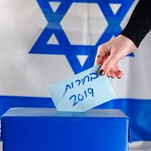 Israeli Woman Votes At A Polling Station On Election Day.close Up Of Hand. Hebrew Text Elections 201 poster