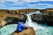 Traveler Hiking In Icelandic Summer Landscape At The Aldeyjarfoss Waterfall In North Iceland. The Wa poster