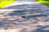 Broken Empty Asphalt Country Road Surrounded By Trees In Sunny Summer Day. Road With Holes In The Gr poster