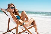 Happy young woman relaxing on deck chair at beach while looking at camera. Mature woman with red hai poster