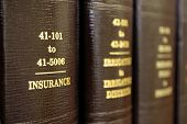 stock photo of law-books  - Close up of several volumes of law books of codes and statutes on insurance - JPG
