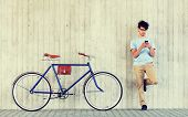 people, communication, technology, leisure and lifestyle - hipster man with smartphone and fixed gea poster