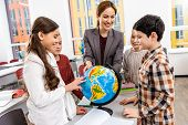 Teacher And Pupils Looking At Globe While Studying Geography In Classroom poster