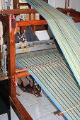 stock photo of handloom  - a lady weaving an bluea and yellow colour fabric - JPG