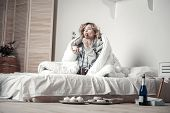 Young Stressed Woman Eating Sweets And Drinking Alcohol In Bed poster