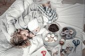 Lonely Stressed Woman Lying In Bed Near Sweets And Photos poster