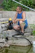 picture of water well  - A man with the electric water pump for watering garden near pond - JPG