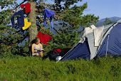 Woman Relaxing By Tent With Clothes Drying