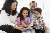 stock photo of close-up middle-aged woman  - Grandparents sitting in living room reading with grandchildren smiling  - JPG