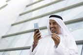 Middle Eastern Business Man Stood Outside Offices With Cell Phone