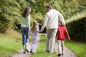 stock photo of tweenie  - Family walking on path outdoors smiling  - JPG