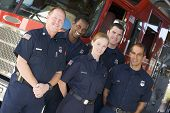 picture of fire-station  - Five firefighters standing in front of fire engine - JPG