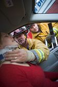 picture of crew cut  - Fireman helping woman with neck brace while another fireman uses the jaws of life on a car door  - JPG