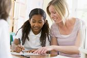 picture of tweeny  - Student in class taking notes with teacher helping - JPG
