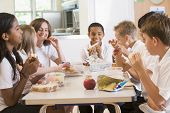 stock photo of tweeny  - Students sitting at cafeteria table eating lunch  - JPG